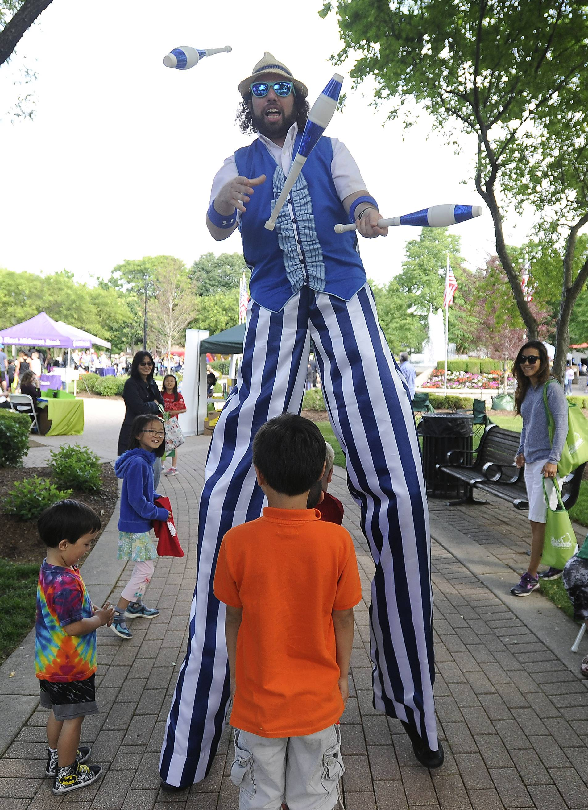 Entertainer Jason Kollum juggles while walking through the crowd of children Friday during Picnic in the Park at North School Park in Arlington Heights.