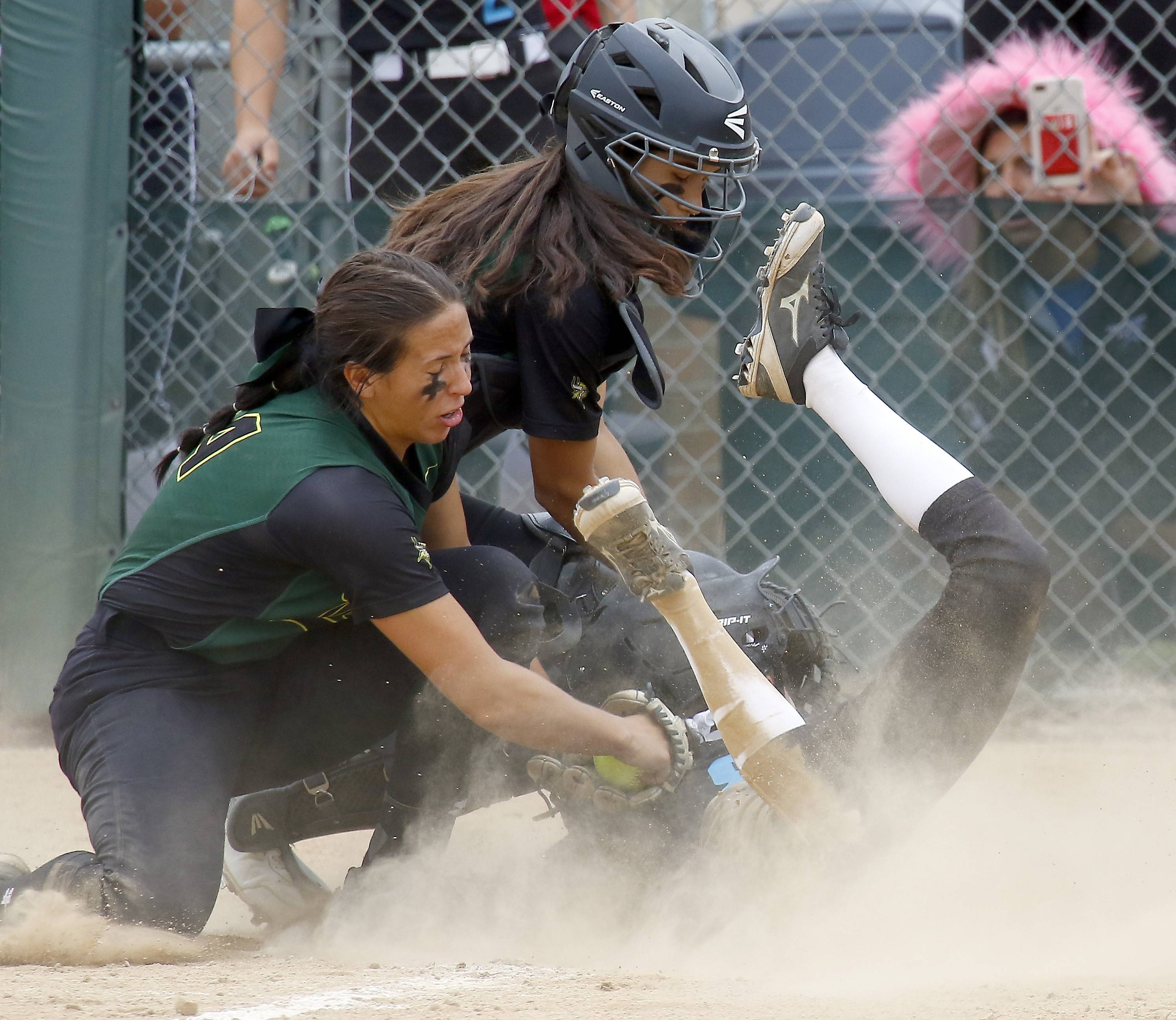 Fremd's Jess Mazur, left, and Fremd's Lexi D'Ambrosio try to put the tag on St. Charles North's Alyssa Domaracki during sectional final play last weekend at Fremd.