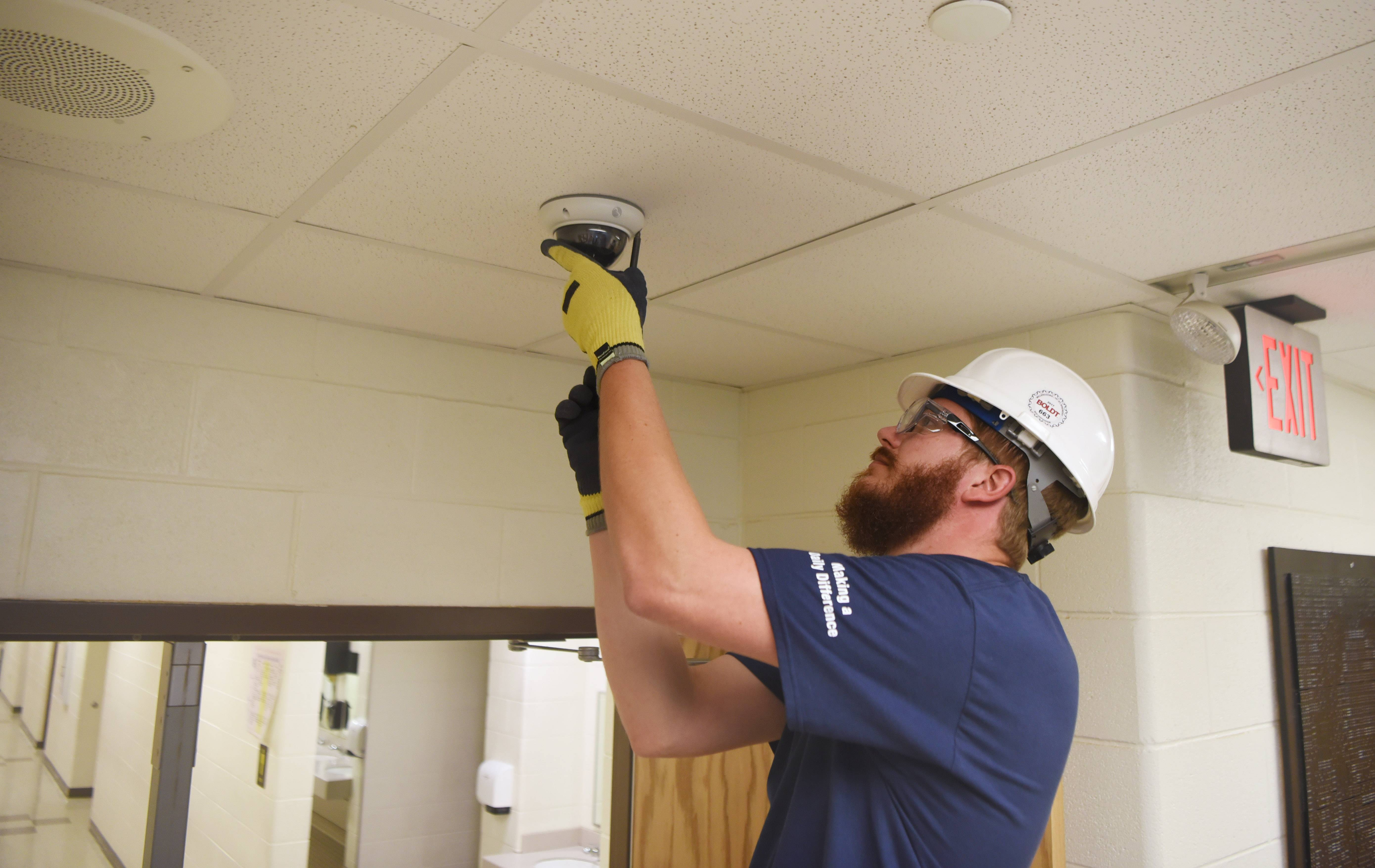 Convergint Technologies employee Cody Hoffman adjusts a security camera inside Waukegan