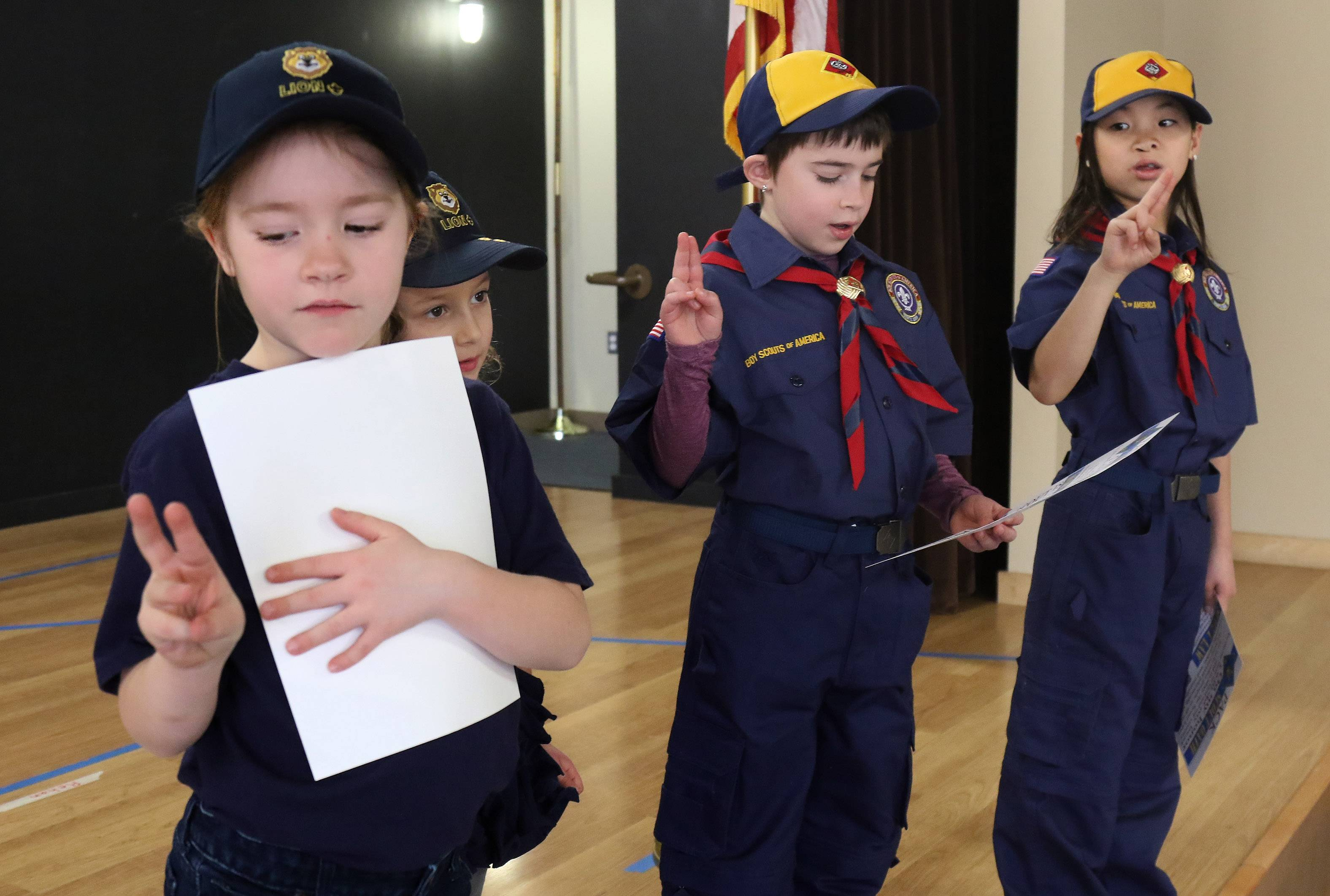 The newest girls in Cub Scouts, Addison Carver, 6, from left, Willow Youkhana, 6, and Kate and Lucy Vraniak, both 8, practice forming their fingers for the salutes they learn for the Scout Oath during the first meeting of Den 9 of Cub Scouts Pack 229 at the Barrington Park District Recreation and Fitness Center in Langendorf Park.