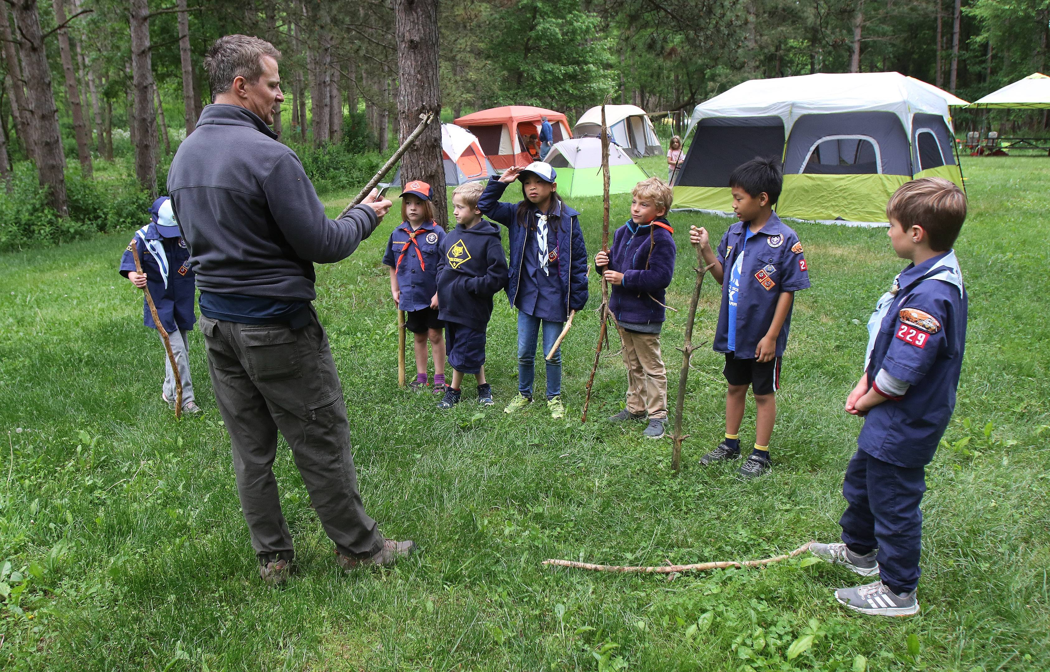 A former Scout and now a dad, Dave Szela talks about knife safety during a campout with Cub Scouts Pack 229 at Kettle Moraine State Forest in Wisconsin. The pack is among the first in the region to include girls.
