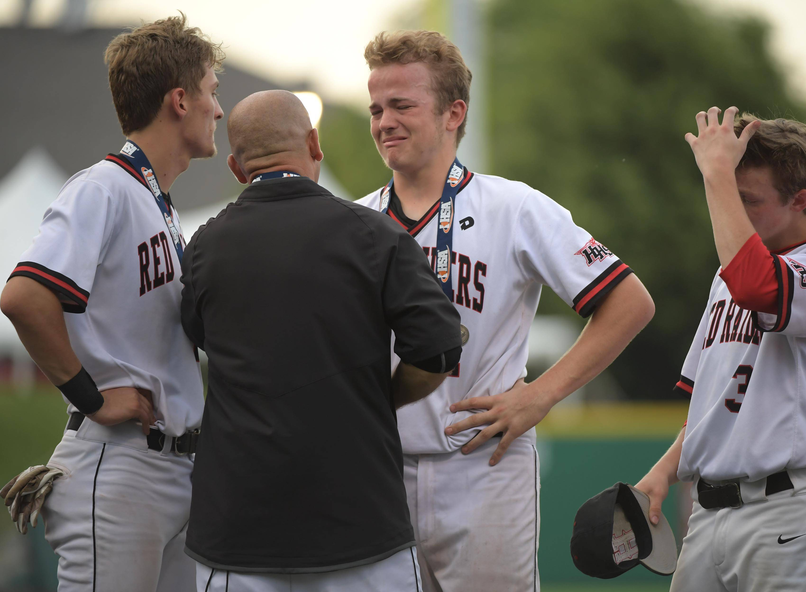 Huntley's A.J. Henkle tries to hold his emotions in check as he is presented a medal from head coach Andy Jakubowski after the loss to Plainfield North in the Class 4A baseball state championship game at Route 66 Stadium in Joliet on Saturday.