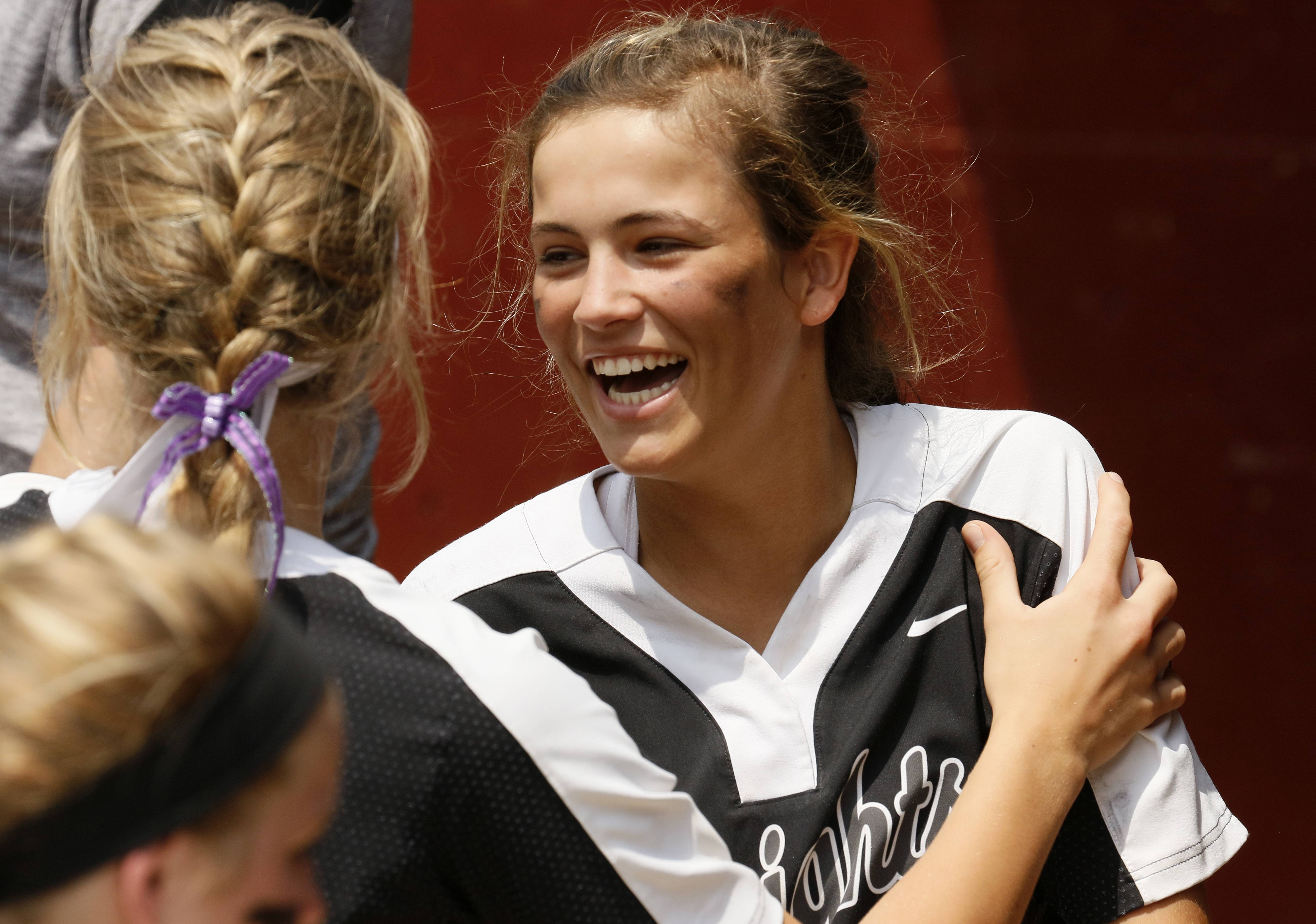 Kaneland's Natalie Kraemer is all smiles in the dugout against Montini Catholic during the IHSA Class 3A state softball championship.