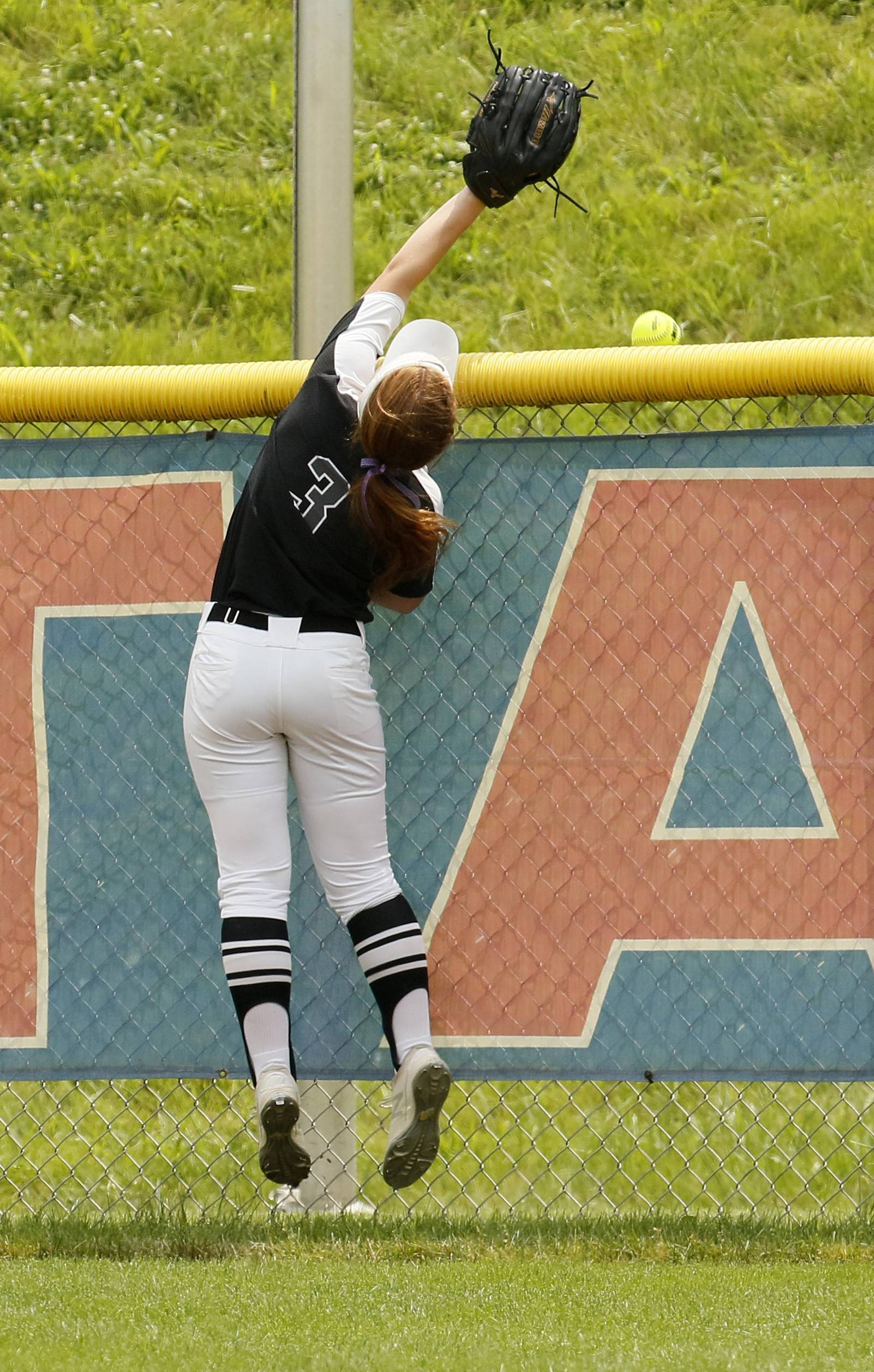 Kaneland center fielder Maddy Wheatley (3) leaps but is unable to catch a Montini Catholic home run during the IHSA Class 3A state softball championship.