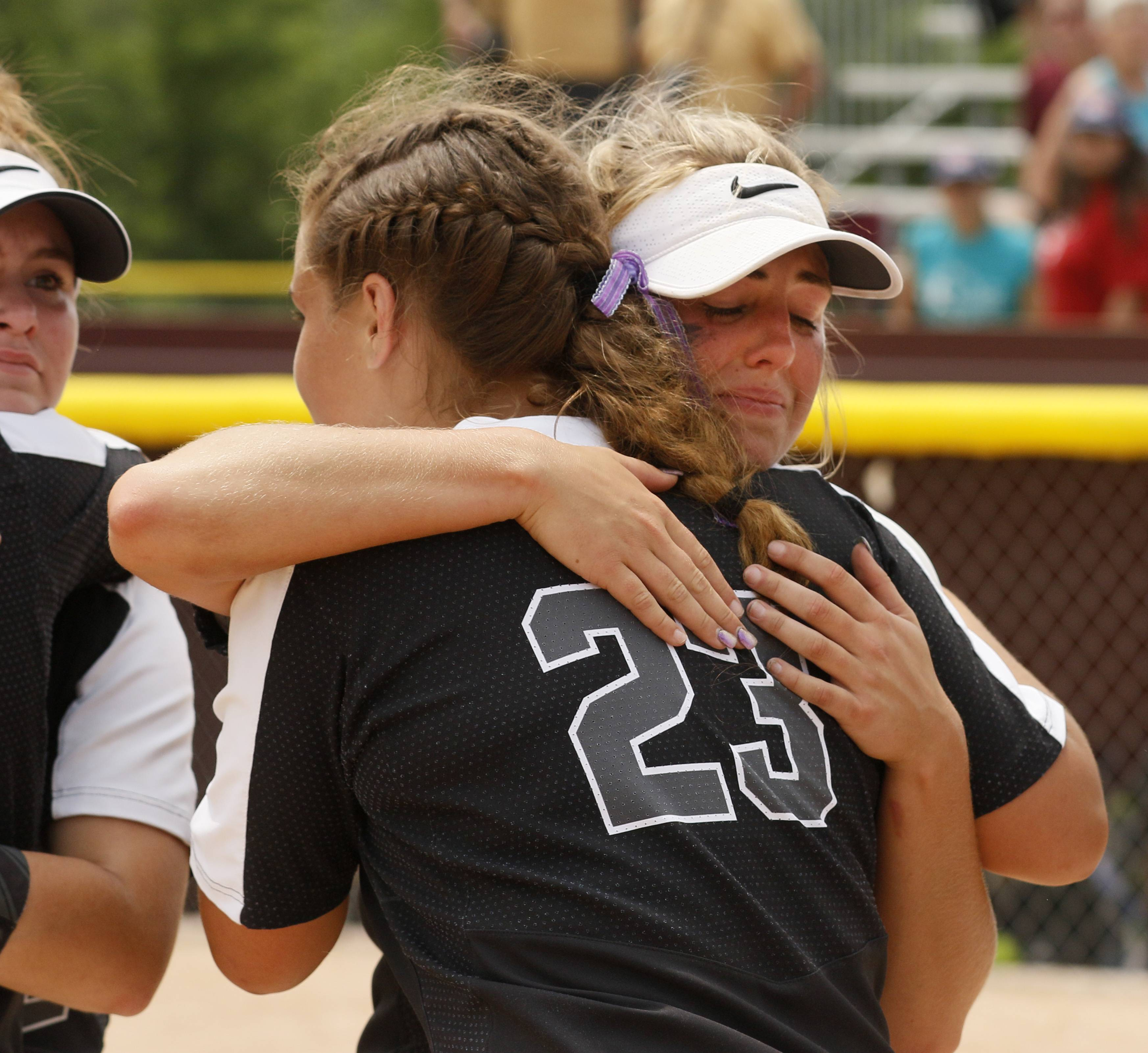 Kaneland players hug each other following the IHSA Class 3A state softball championship game.
