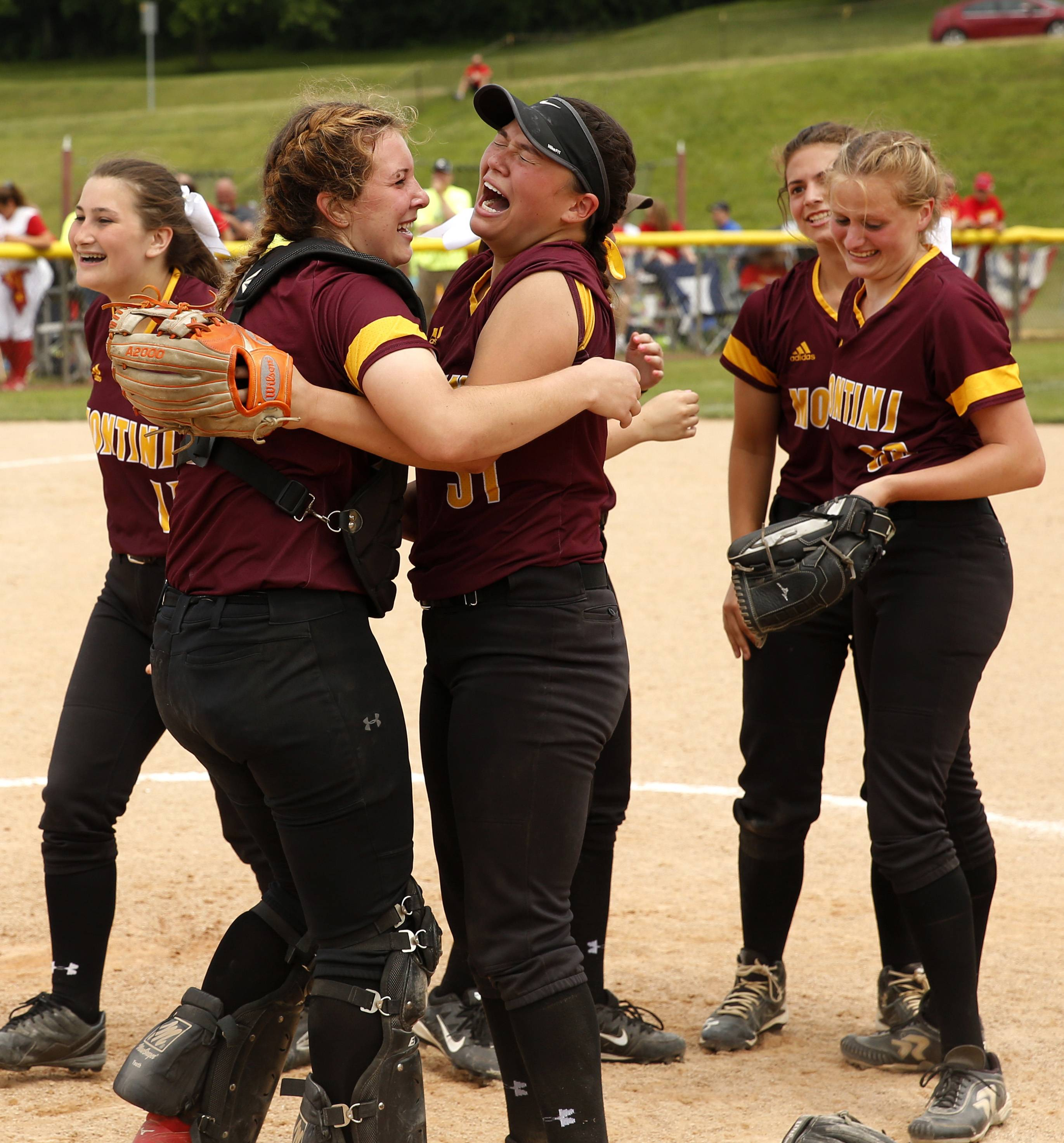 Montini Catholic players celebrate their epic 15-8 seventh inning comeback against Kaneland to win the IHSA Class 3A state softball championship.