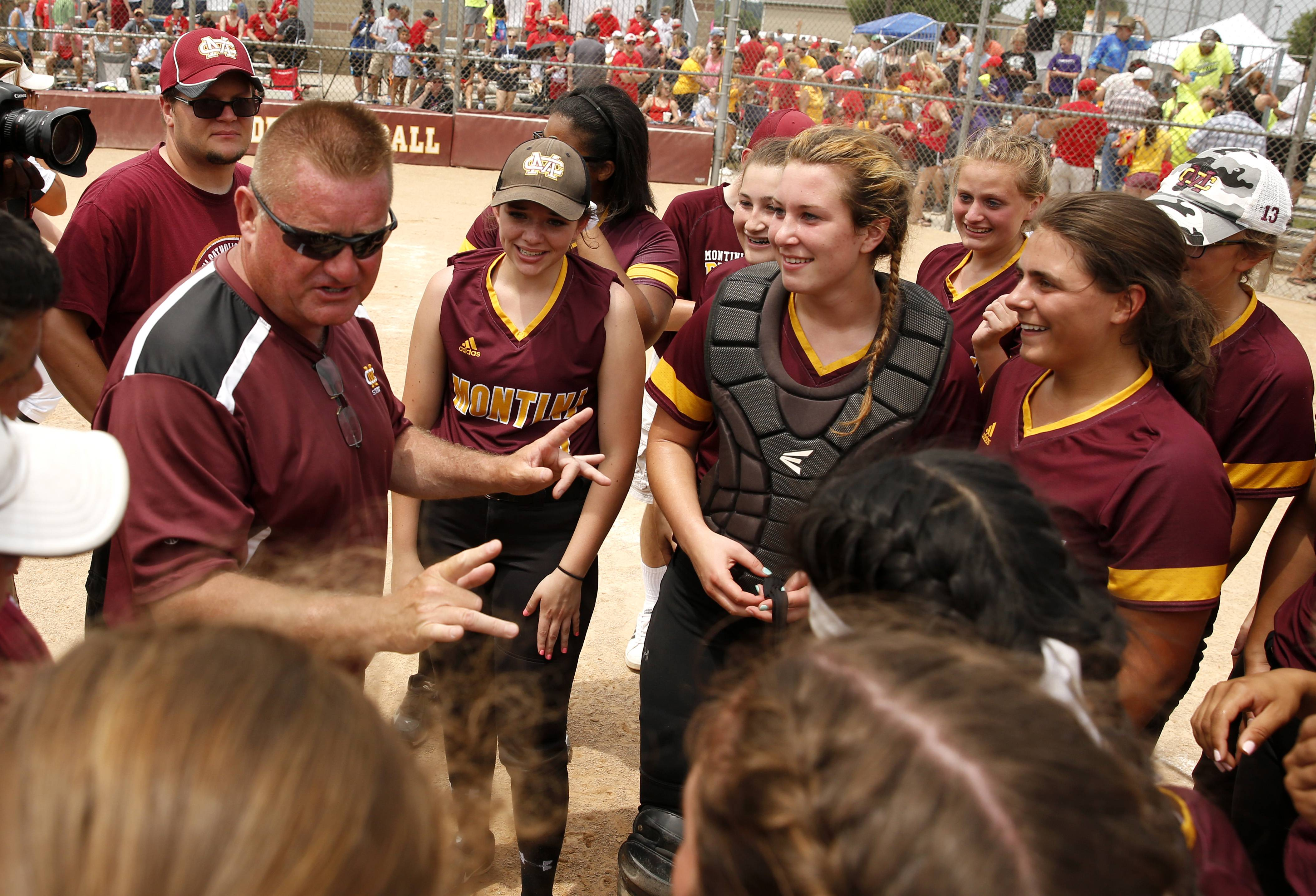 Montini Catholic coach Mike Bukovsky talks to his players after their epic 15-8 seventh inning comeback against Kaneland to win the IHSA Class 3A state softball championship.