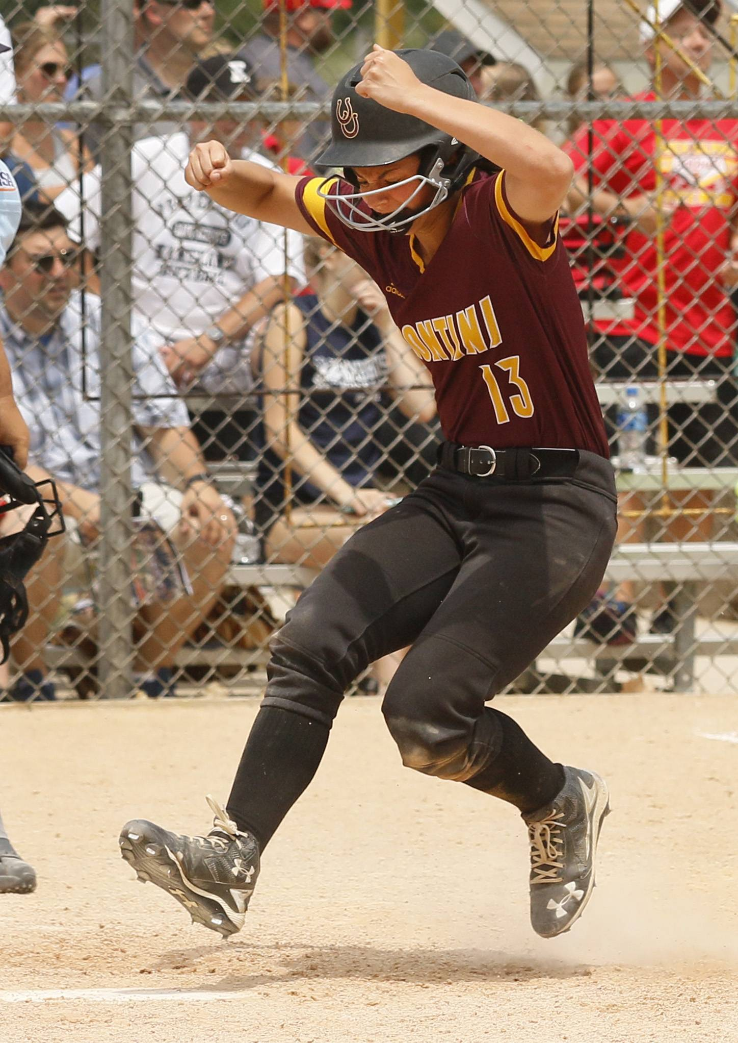 Montini Catholic's Madalyn Rawski (13) celebrates scoring a run during the Bronco's epic 15-8 seventh inning comeback against Kaneland to win the IHSA Class 3A state softball championship.