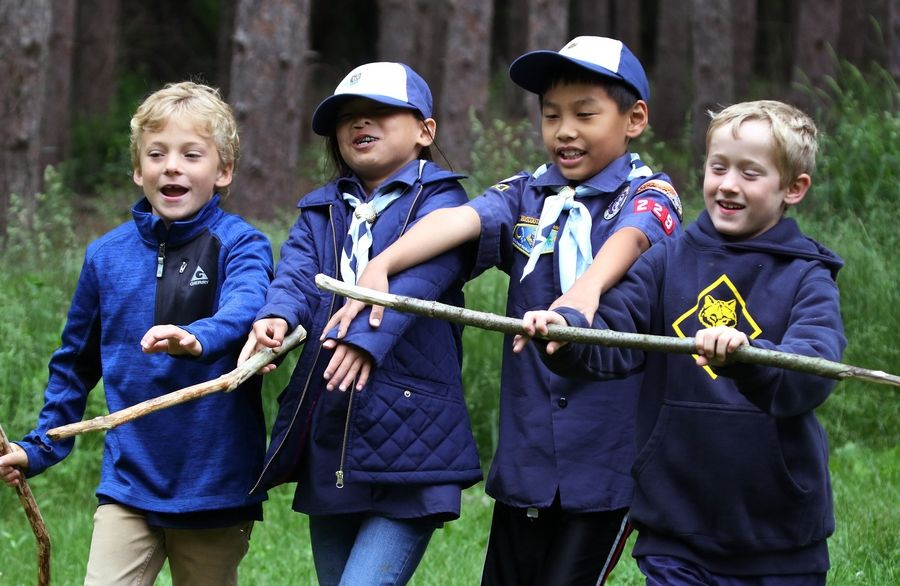Nick Szela, left, Lucy Vraniak, George Kircher and Caden Carver play a game as they march in the woods during a campout with Cub Scouts Pack 229 at Kettle Moraine State Forest in Wisconsin.