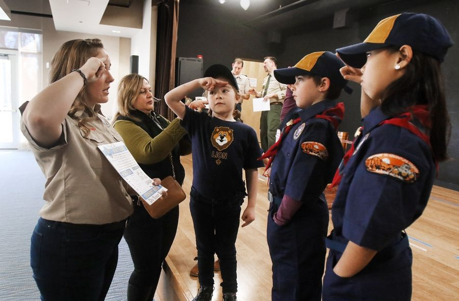 "Cub Scout leader Laurie Carver of Lake Barrington teaches a salute to new scouts, Addison Carver, 6, and Kate and Lucy Vraniak, both 8, of Tower Lakes, during the first meeting of Den 9 in Cub Scouts Pack 229. This den is among three ""early adopter"" units in the area that began including girls for the first time earlier this year."