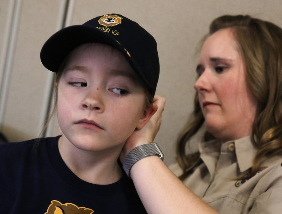 "New Cub Scout Addison Carver, 6, of Lake Barrington gets help with her hair and cap from her mother and Cub Scout leader, Laurie Carver, during the first meeting of Den 9 of Pack 229. While the pack is one of three ""early adopters"" to allow girls, all Cub Scouting units in the region will be open to female participants ages 5 to 10 beginning June 11."