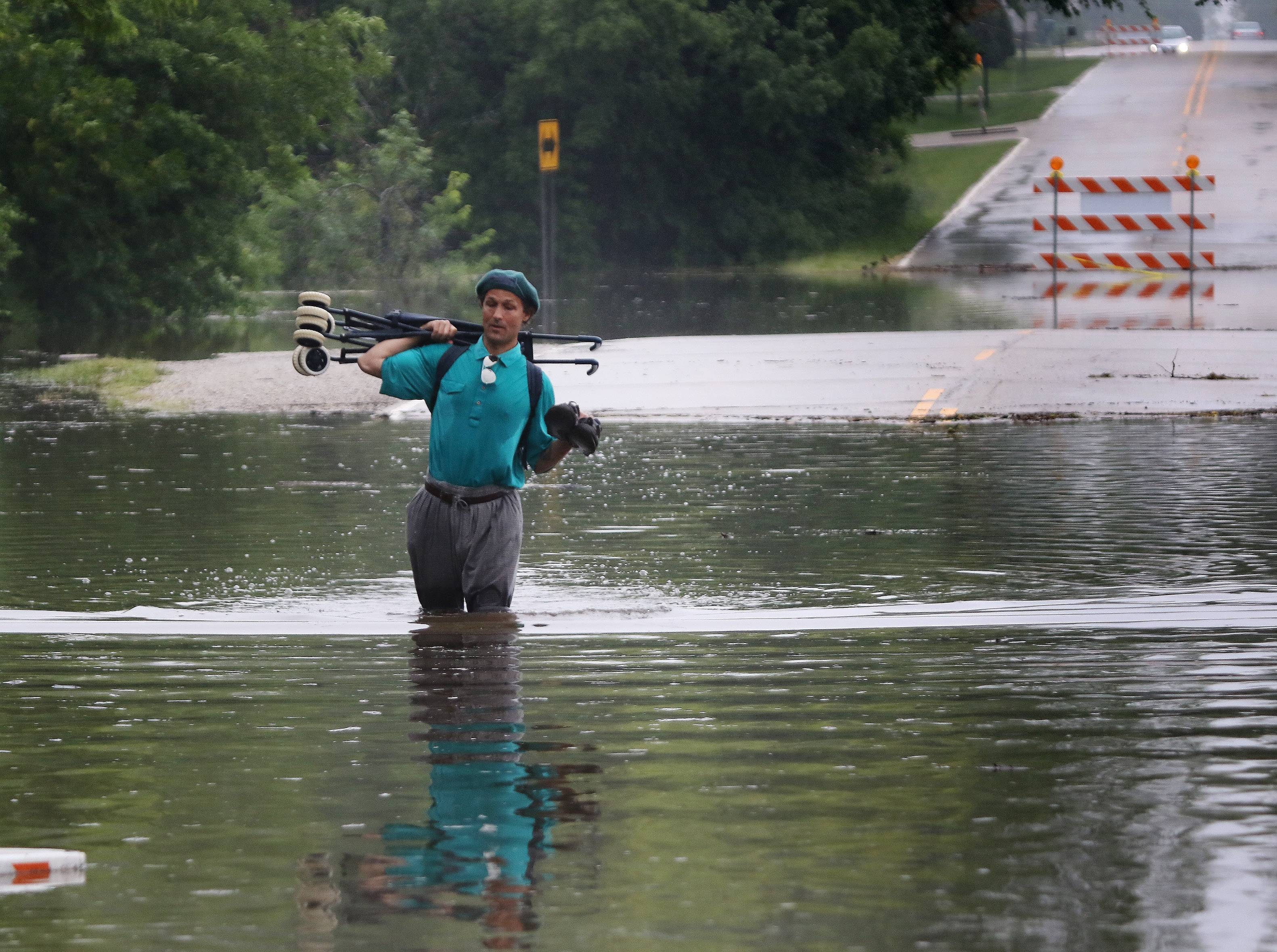 Prospect Heights resident Jonathan Bordner walks Sunday through floodwaters on Hillside Avenue near Willow Road.