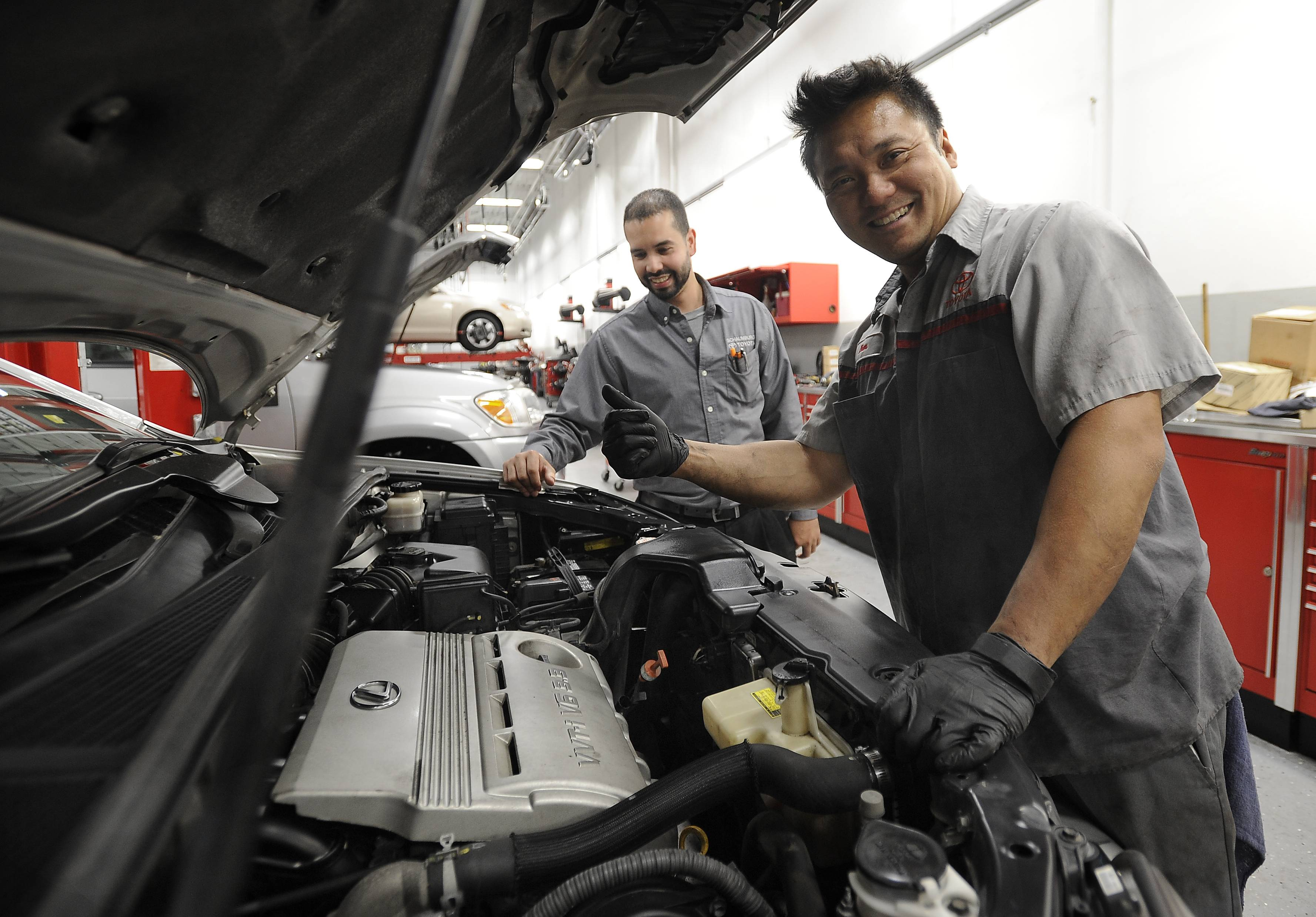 Schaumburg Toyota service technician Anthony Mejias, Assistant Service Manager (back) with Bien Arquiza, Master Technician at the dealership. All cars at the tent sale this week have been given a full inspection that covers 100 items.