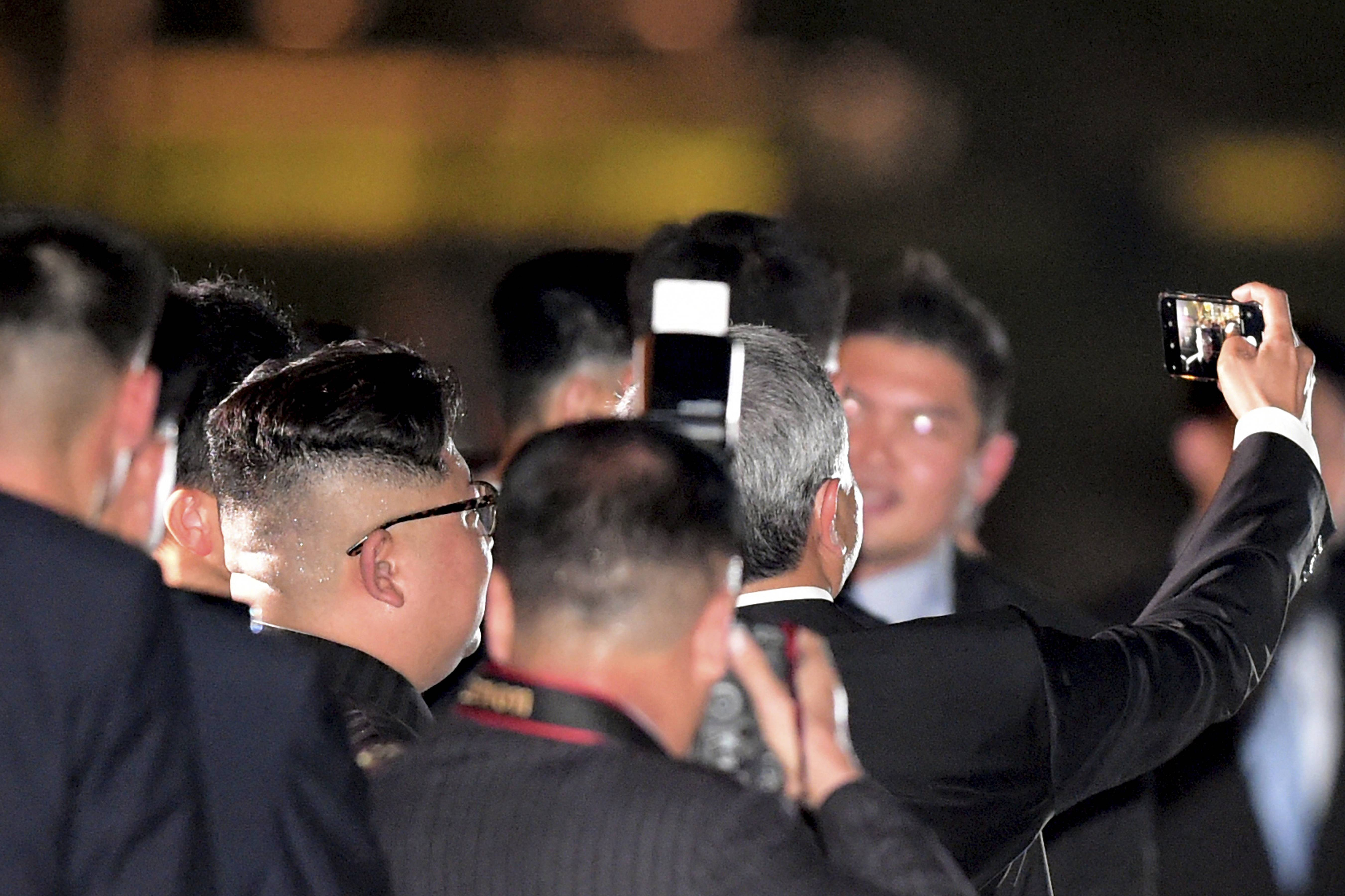 North Korean leader Kim Jong Un, seen from back, takes a selfie with Singapore Foreign Minister Vivian Balakrishnan as they walk on the Jubilee Bridge as he tours Singapore on Monday ahead of the summit between U.S. leader Trump and North Korea leader Kim Jong Un.