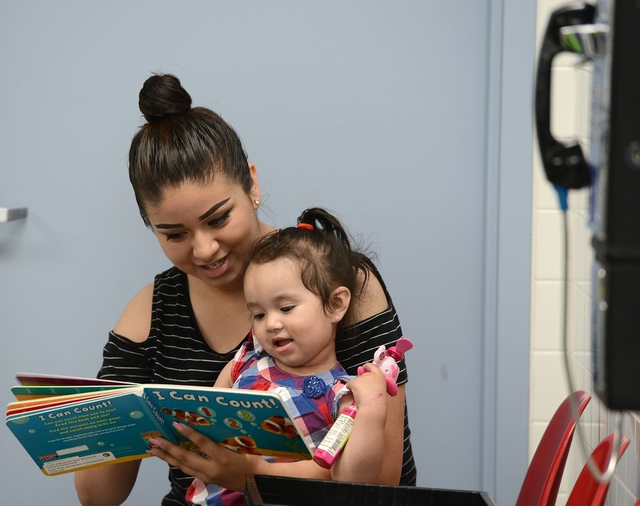 Maria Garnica of Elgin reads to her 17-month-old daughter, Melanie Rios, at the JetXpress Laundromat in Elgin. A library was set up there by the Elgin Partnership for Early Learning to promote literacy targeting at-risk families.