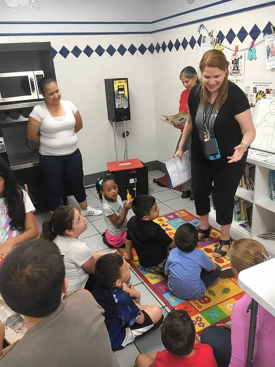 "Madeleine Villalobos, right, from the Gail Borden Public Library in Elgin, and two adult volunteer readers conduct storytime in a corner of the JetXpress Laundromat in Elgin as part of the ""Language in the Laundromat"" program promoting early learning."