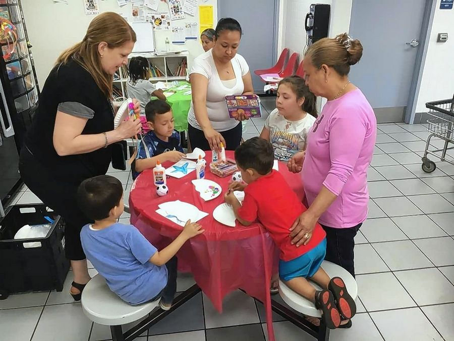 "Madeleine Villalobos, left, from the Gail Borden Public Library in Elgin, and two adult volunteer readers work on crafts with children at the JetXpress Laundromat in Elgin as part of the ""Language in the Laundromat"" program."