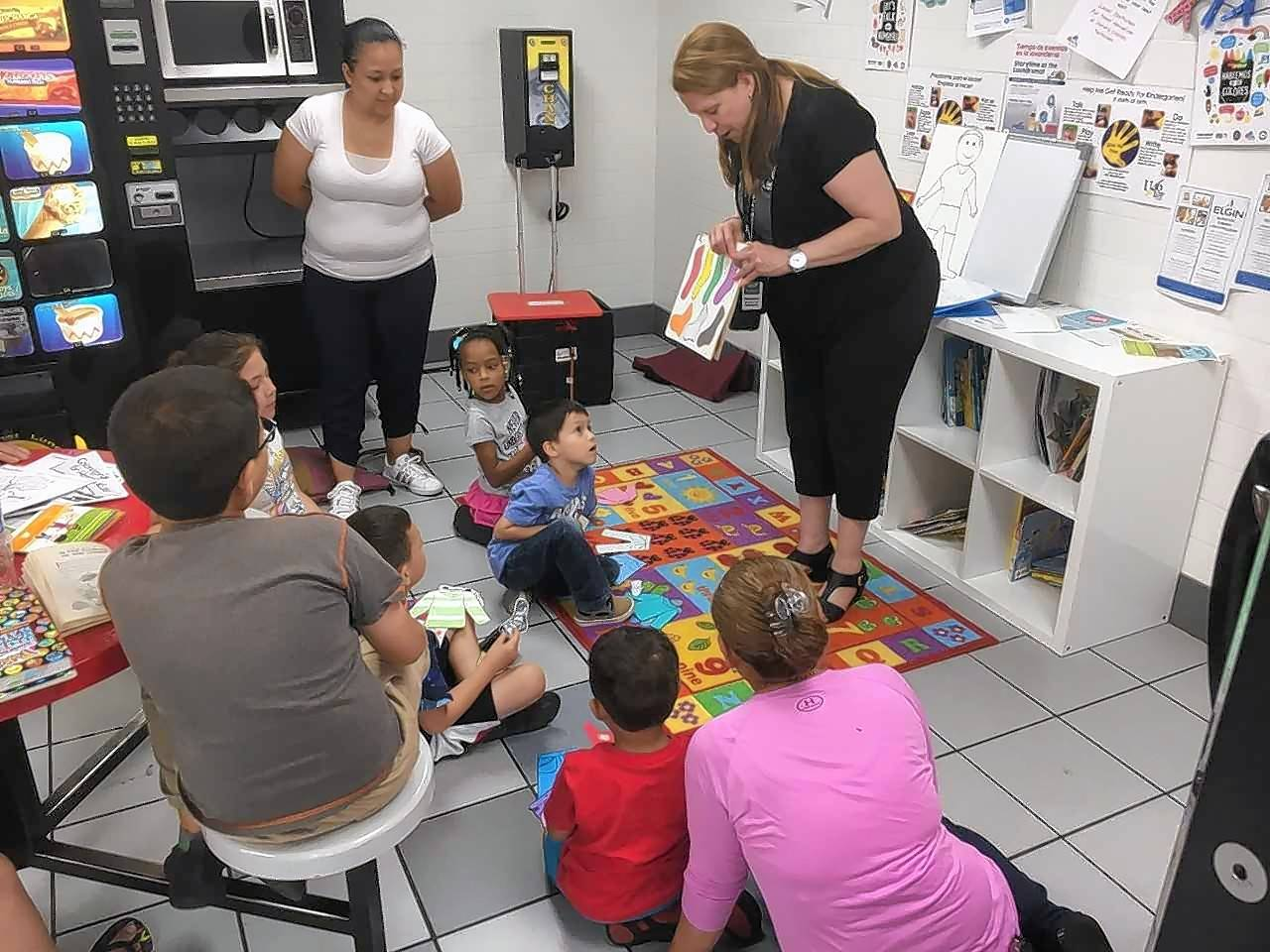 "Madeleine Villalobos, right, from the Gail Borden Public Library in Elgin, and an adult volunteer reader conduct storytime at the JetXpress Laundromat in Elgin as part of the ""Language in the Laundromat"" program promoting reading."