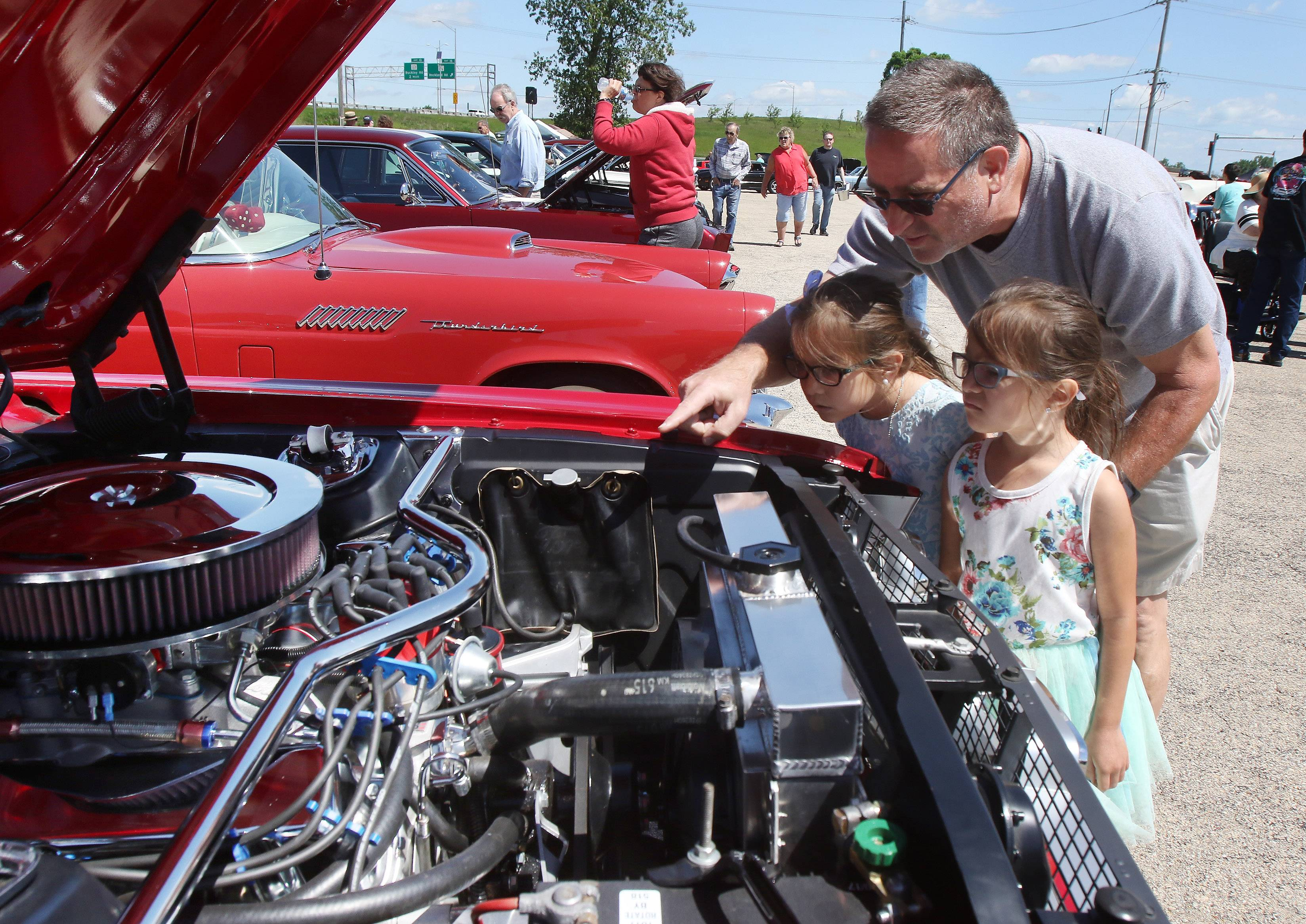 Ken Abbott, of Green Oaks shows his 6-year-old twin daughters, Gracie and Glory, the engine of a 1967 Ford Mustang during the 6th annual Lambs Farm Champion Car Show on Sunday in Libertyville.