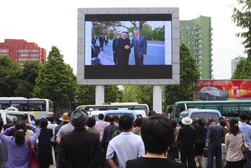 People watch a large screen at the main train station airing video of North Korean leader Kim Jong Un being greeted by Singapore Prime Minister Lee Hsien Loong in Pyongyang, North Korea, Monday, June 11, 2018.