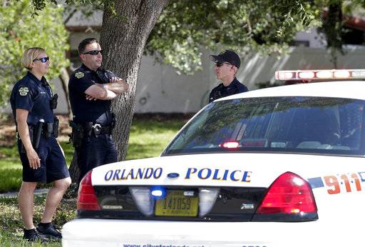 Orlando Police block an intersection leading to an apartment complex where an officer was shot and seriously wounded before the gunman barricaded himself in an apartment with young children. Monday, June 11, 2018, in Orlando, Fla.