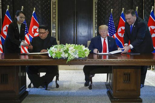 North Korea leader Kim Jong Un and U.S. President Donald Trump prepare to sign a document at the Capella resort on Sentosa Island Tuesday, June 12, 2018 in Singapore.