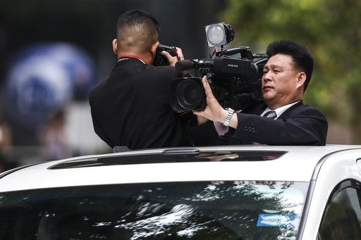 North Korean journalists film the motorcade of North Korea leader Kim Jong Un as they leave the St. Regis Hotel on the way to the Capella Hotel in Singapore, Tuesday, June 12, 2018, where the summit between Kim and U.S. President Donald Trump will take place.