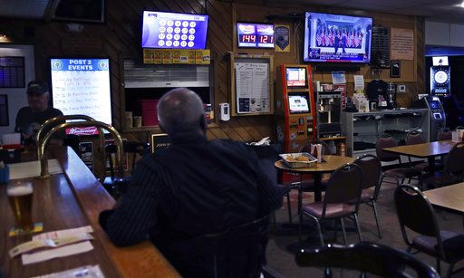 John Miller, of Manchester, N.H., a former U.S. Army sergeant who served as a forward radio relay operator in Vietnam, watches as President Donald Trump shakes hands with North Korean leader Kim Jong Un, while having a beer at the American Legion Post #2 in Manchester on Monday, June 11, 2018.