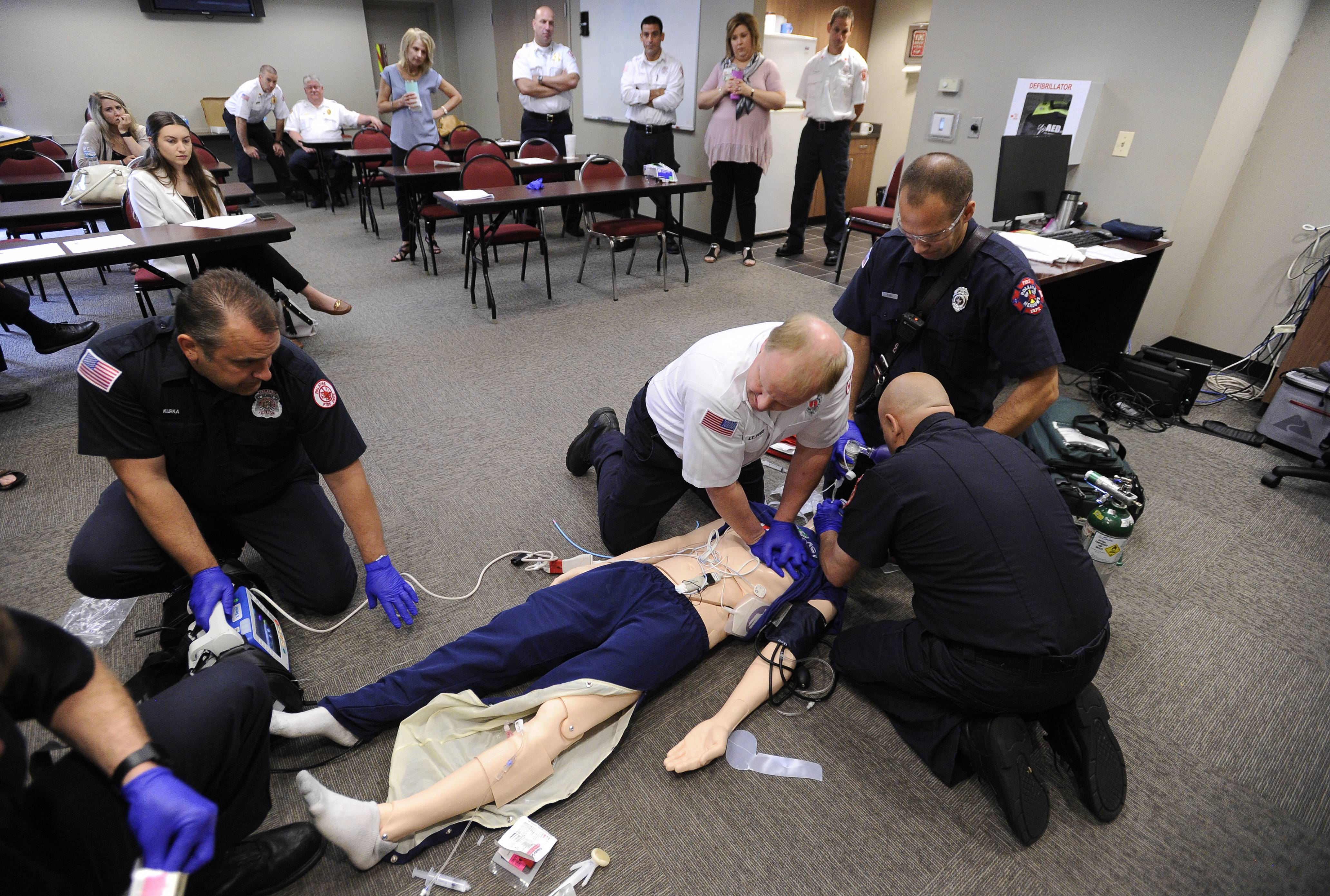 Palatine Rural Fire Protection District Lt. Roger Fyke performs chest compressions Tuesday as other first responders from Palatine and Rolling Meadows fire departments work on a new training manikin.