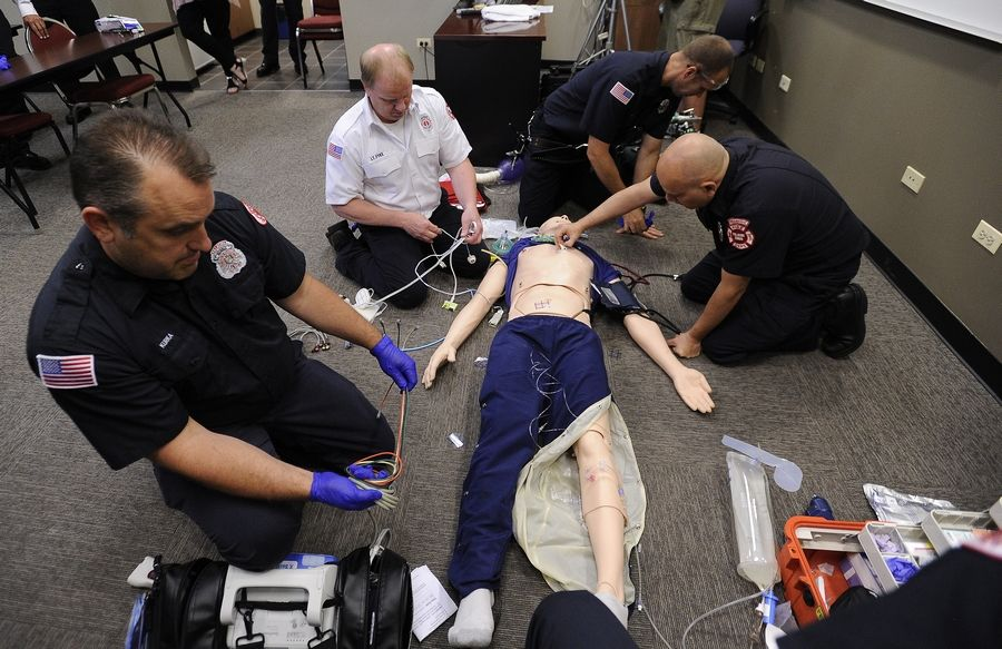 Palatine and Rolling Meadows fire department first responders work on their new training manikin Tuesday.