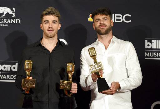 "FILE - In this May 20, 2018, file photo, Andrew Taggart, left, and Alex Pall of ""The Chainsmokers"" pose in the press room with the awards for top dance/electronic artist, top dance/electronic song for ""Something Just Like This"" and top dance/electronic album ""Memories…Do Not Open"" at the Billboard Music Awards at the MGM Grand Garden Arena in Las Vegas. The Chainsmokers is looking to mesh their EDM-style with some of the most popular songs from Michael Jackson to Beyonce during one-night only performance in July. Tickets for the event go on sale on Wednesday, June 13. (Photo by Jordan Strauss/Invision/AP, File)"