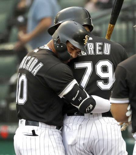 Chicago White Sox's Yoan Moncada, left, hugs Jose Abreu after Moncada's home run off Cleveland Indians starting pitcher Adam Plutko during the first inning of a baseball game Tuesday, June 12, 2018, in Chicago.