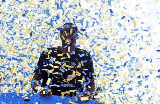 Confetti comes down on Golden State Warriors' Draymond Green (23) is surrounded by confetti during the team's NBA basketball championship parade, Tuesday, June 12, 2018, in Oakland, Calif.