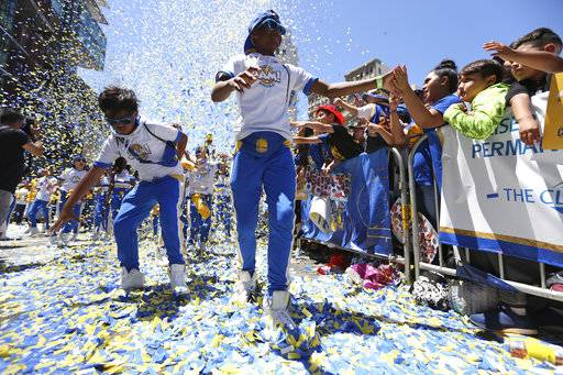 Andre Fangonilo, left, and Paris Jackson, Jr., both 12, greet fans in the crowd as they dance during the Golden State Warriors' NBA basketball championship parade, Tuesday, June 12, 2018, in Oakland, Calif. The two are part of the team's Junior Jam squad.