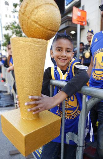 Brandon Singh waits with his trophy for the parade to start in honor of the NBA basketball champion Golden State Warriors, Tuesday, June 12, 2018, in Oakland, Calif.