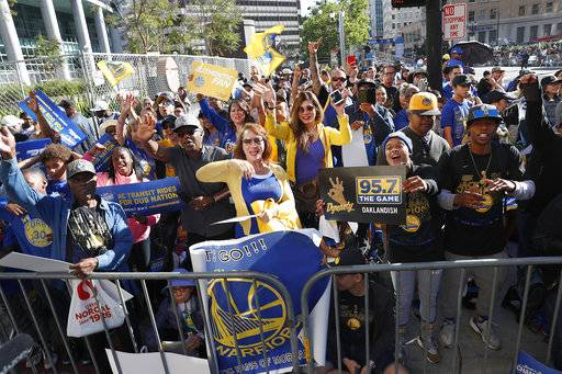 Fans wait for the parade to start in honor of the Golden State Warriors, Tuesday, June 12, 2018, in Oakland, Calif., to celebrate the team's NBA basketball championship.