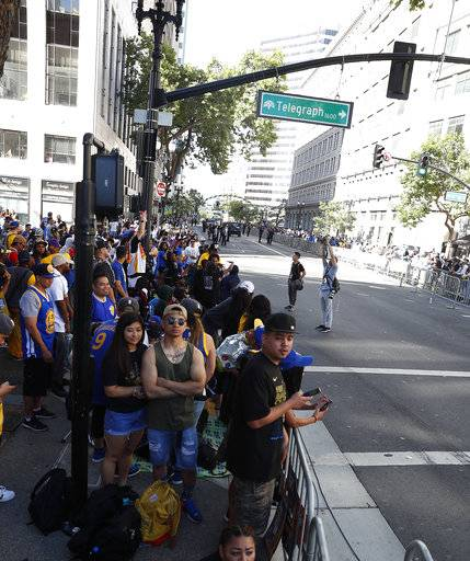 Fans line the streets as they wait for the parade to start in honor of the NBA basketball champion Golden State Warriors, Tuesday, June 12, 2018, in Oakland, Calif.
