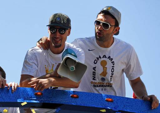 Golden State Warriors' Klay Thompson, left, and Zaza Pachulia ride together during the team's NBA basketball championship parade, Tuesday, June 12, 2018, in Oakland, Calif.