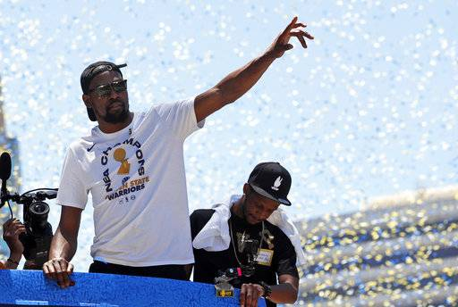 Golden State Warriors' Kevin Durant waves to fans during the team's NBA basketball championship parade, Tuesday, June 12, 2018, in Oakland, Calif.