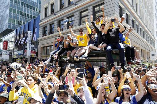Fans watch as the Golden State Warriors pass by during the team's NBA basketball championship parade, Tuesday, June 12, 2018, in Oakland, Calif.