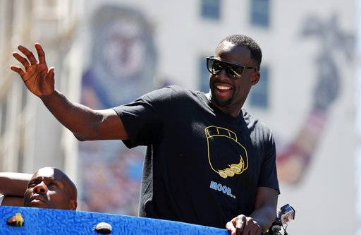 Golden State Warriors' Draymond Green waves to fans during the team's NBA basketball championship parade, Tuesday, June 12, 2018, in Oakland, Calif.