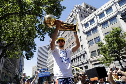 Golden State Warriors' Stephen Curry holds the Larry O'Brien trophy during the team's NBA basketball championship parade, Tuesday, June 12, 2018, in Oakland, Calif.