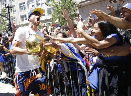 Golden State Warriors' Stephen Curry carries the Larry O'Brien trophy as he celebrates with fans during the team's NBA basketball championship parade, Tuesday, June 12, 2018, in Oakland, Calif.