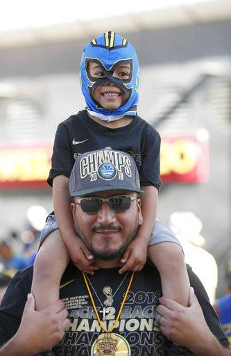Jose Gutierrez and his son Noah wait for the parade to start in honor of the NBA basketball champion Golden State Warriors, Tuesday, June 12, 2018, in Oakland, Calif.