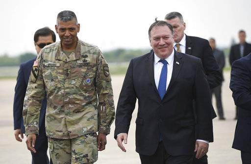U.S. Secretary of State Mike Pompeo, right, walks with U.S. General Vincent K. Brooks, left, commander of United States Forces Korea, upon his arrival at Osan Air Base in Pyeongtaek Wednesday, June 13, 2018.  South Korea's presidential office said Pompeo will meet President Moon Jae-in Thursday morning to discuss the meeting, which made history as the first between sitting leaders of the U.S. and North Korea. (Jung Yeon-je/Pool Photo via AP)