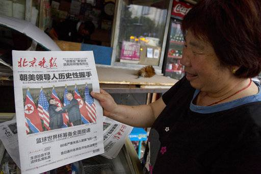 "FILE - In this June 12, 2018, file photo, a newspaper vendor holds up a front page photo of the meeting in Singapore between U.S. President Donald Trump and North Korean leader Kim Jong Un at a newsstand in Beijing, China. As soon as Kim steps off the airplane China provided him for the Singapore trip, Beijing will be mindful of maintaining its influence over a Pyongyang that may feel less isolated after Trump showered Kim with praises, called him a ""very talented man,� and made security concessions in return for very little."