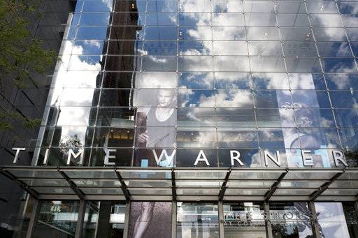 FILE - In this Oct. 24, 2016, file photo, clouds are reflected in the glass facade of the Time Warner building in New York. The judge presiding over the government's legal effort to block AT&T's purchase of Time Warner will likely deliver his verdict on Tuesday, June 12, 2018.