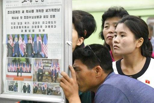 People look at the display of local newspaper reporting the meeting between North Korean leader Kim Jong Un and U.S. President Donald Trump, at a subway station in Pyongyang, North Korea Wednesday, June 13, 2018. The series of photos on the front page of the ruling workers' party newspaper showed something North Koreans never would have imagined just months ago, their leader Kim warmly shaking hands with Trump. (Minoru Iwasaki/Kyodo News via AP)