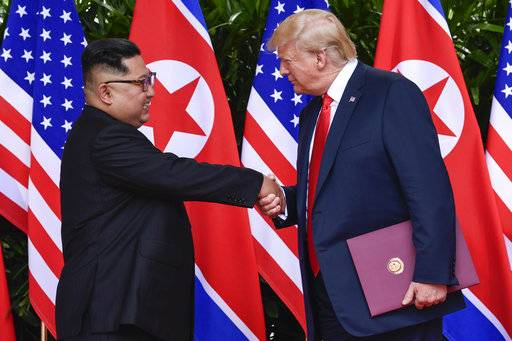 FILE - In this June 12, 2018, file photo, North Korea leader Kim Jong Un, left, and U.S. President Donald Trump shake hands at the conclusion of their meetings at the Capella resort on Sentosa Island in Singapore. The series of photos on the front page of the ruling workers' party newspaper showed something North Koreans never would have imagined just months ago, their leader Kim Jong Un warmly shaking hands with President Donald Trump.