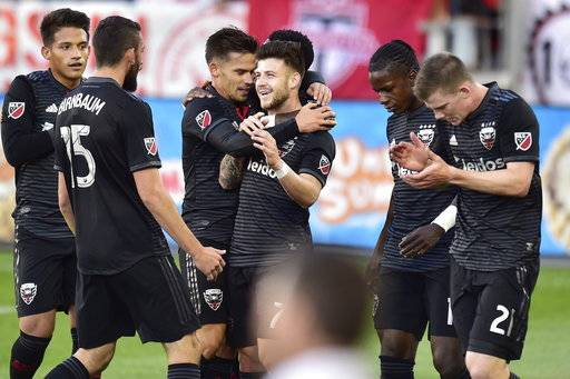 D.C. United forward Paul Arriola, center, celebrates his goal with teammates during the first half of an MLS soccer match against Toronto FC on Wednesday, June 13, 2018, in Toronto. (Frank Gunn/The Canadian Press via AP)